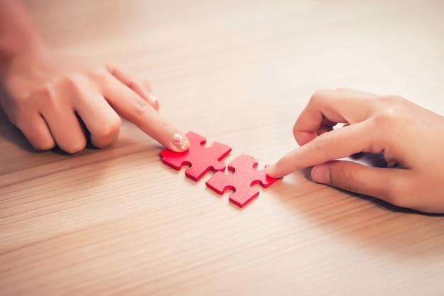 Pezzi del puzzle della tenuta della mano delle donne in ufficio Foto Premium