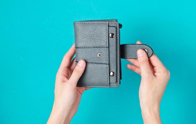 Le mani delle donne aprono il portafoglio in pelle sull'azzurro. Foto Premium
