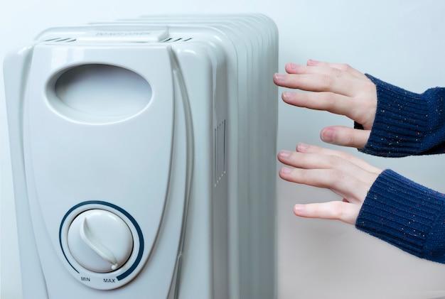 Le mani delle donne raggiungono il radiatore per riscaldarsi Foto Premium