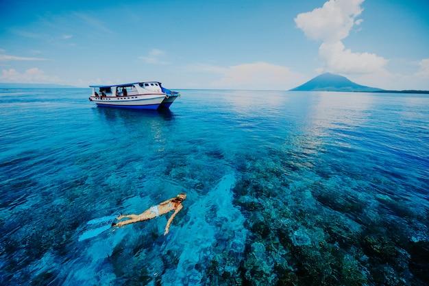 Donne che navigano usando una presa d'aria nel bello mare blu dal lato della montagna di krakatau con una barca pendente Foto Premium