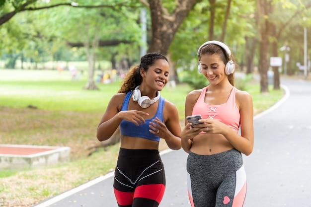 Donne che camminano e fanno jogging regolarmente per la salute nel parco e ascoltano musica rilassante. Foto Premium