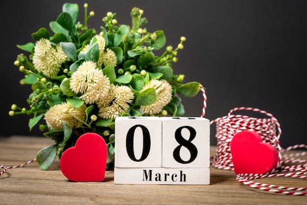 Womens day sfondo con spazio di copia calendario di fiori e cuori su un tavolo di legno Foto Premium