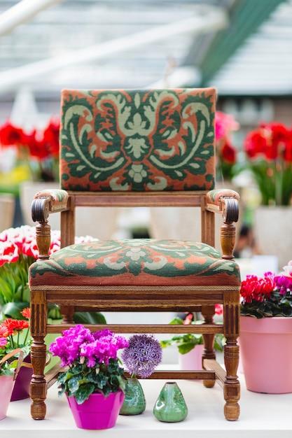 Poltroncina in legno con rivestimento in tessuto e fiori sullo sfondo Foto Premium