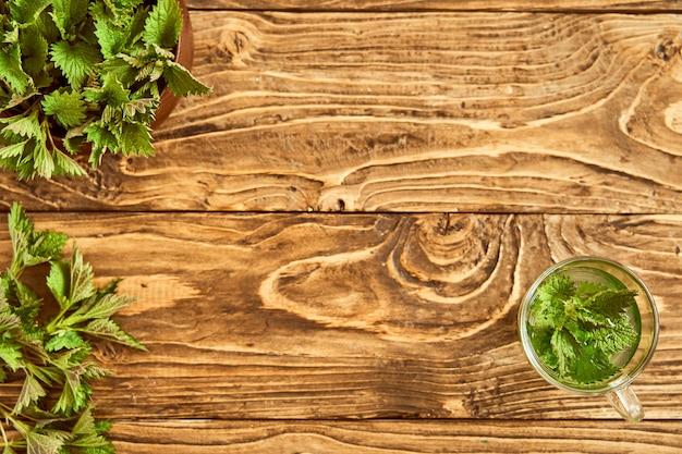 Su uno sfondo di legno è un bicchiere con giovani ortiche preparate. brodo medicinale di ortica. tisana vitaminica. tintura di ortica. la vista dall'alto Foto Premium