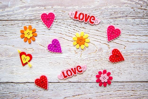 Fondo in legno con cuori, fiori e la parola amore il giorno di san valentino Foto Premium