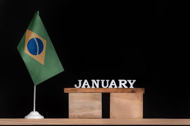 Calendario in legno di gennaio con bandiera brasiliana su uno spazio nero. date del brasile a gennaio. Foto Premium