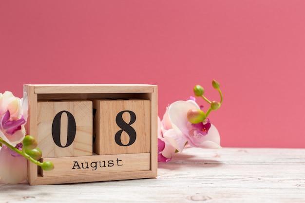 Calendario in legno a forma di cubo per l'8 agosto sul tavolo di legno Foto Premium