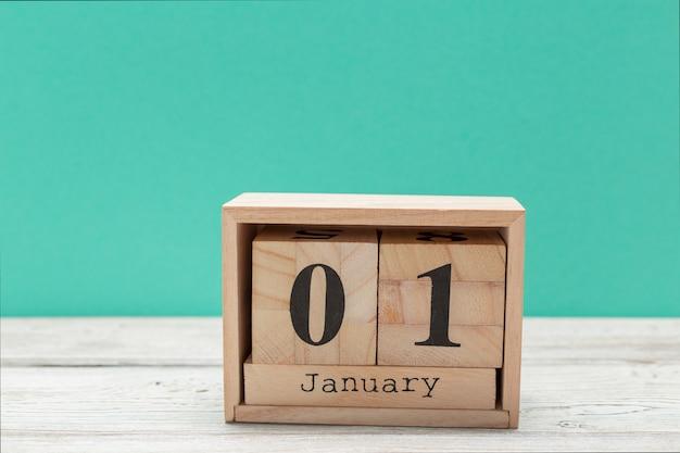Calendario in legno a forma di cubo per il 1 gennaio sul tavolo di legno Foto Premium