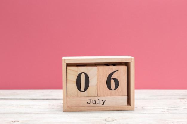 Calendario in legno a forma di cubo per il 6 luglio sul tavolo di legno Foto Premium