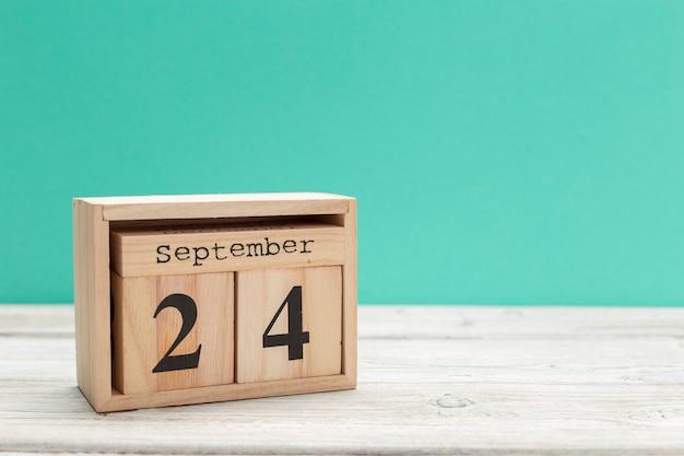 Calendario a forma di cubo di legno per il 24 settembre sul tavolo di legno Foto Premium