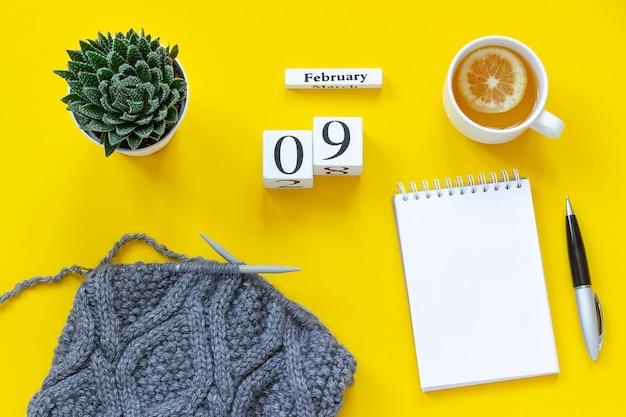 Calendario di cubi di legno 9 febbraio. tazza di tè al limone, blocco note aperto vuoto per il testo. Foto Premium