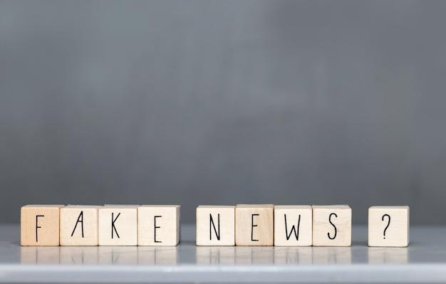 Cubetto di legno con le parole notizie false sulla parete grigia, social media di concetto di notizie false Foto Premium
