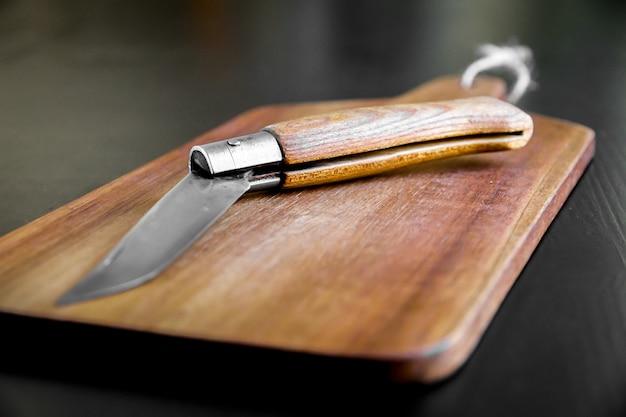 Tagliere di legno e coltellino tascabile su un tavolo da cucina nero Foto Premium