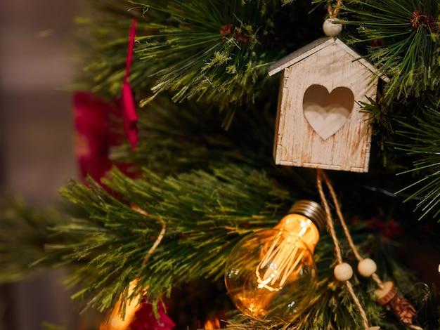 Giocattoli di natale del cuore di legno e torce elettriche sull'albero di natale Foto Premium