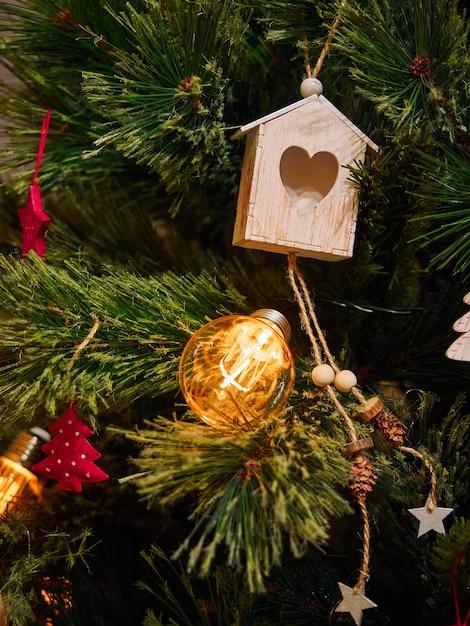 Giocattoli di legno del cuore e torce elettriche sull'albero di natale Foto Premium