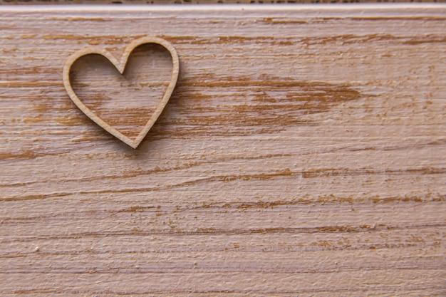 Cuore in legno su fondo in legno Foto Premium