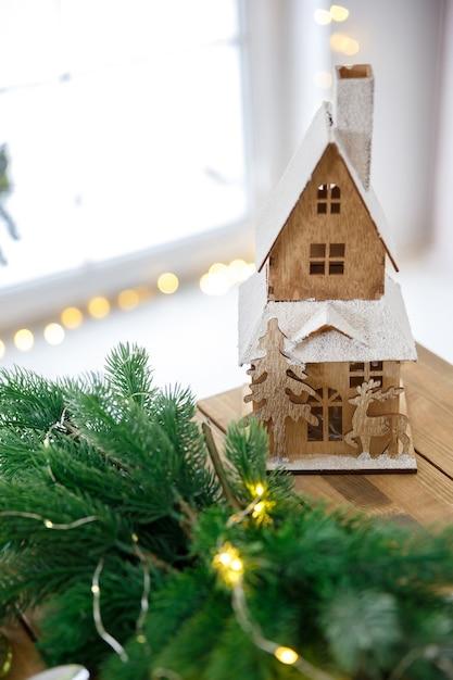 Casa in legno sul vecchio tavolo ruvido decorato con rami di abete Foto Premium