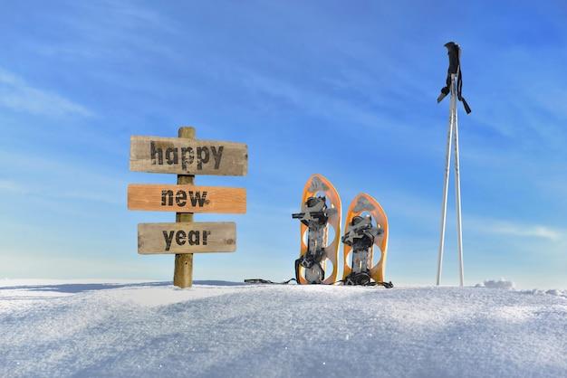 Cartello in legno con testo felice anno nuovo sulla neve accanto a racchette da neve e bastoncini da sci Foto Premium