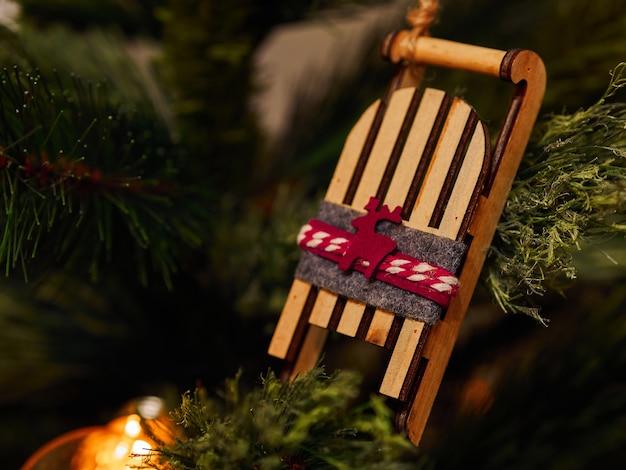 Giocattoli di natale con la slitta in legno e torce elettriche sull'albero di natale Foto Premium