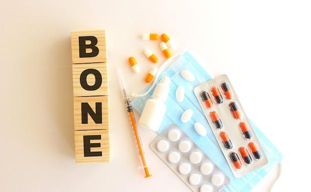 La parola bone è composta da cubi di legno su fondo bianco con farmaci e mascherina medica. Foto Premium
