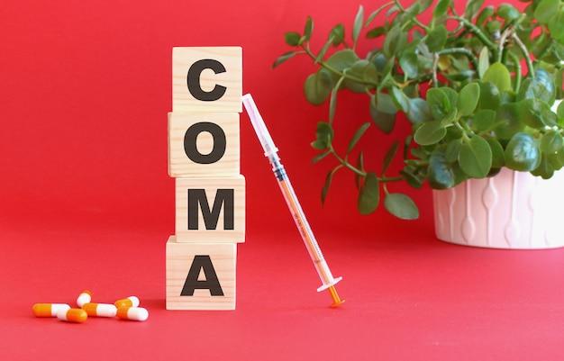 La parola coma è composta da cubi di legno su fondo rosso con farmaci. Foto Premium