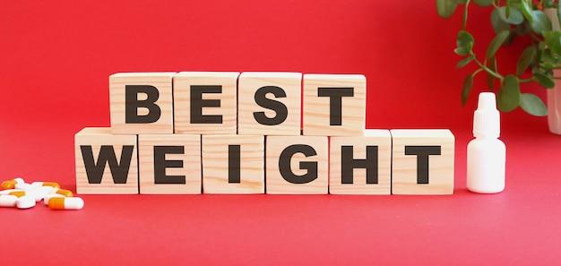 La scritta miglior peso è composta da cubi di legno su sfondo rosso con farmaci. Foto Premium