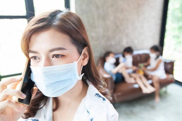 Lavoro da casa donna in quarantena per coronavirus covid-19 con maschera protettiva che parla al telefono e lavora a casa mentre i suoi figli giocano a casa durante l'epidemia di coronavirus Foto Premium