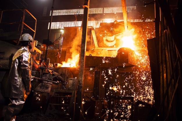 Operaio in tuta di protezione alluminata in piedi dalla fornace con ferro fuso caldo e scintille volanti, fonderia e produzione di acciaio industriale. Foto Premium