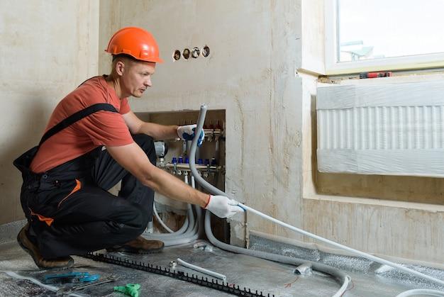 Lavoratore che installa un tubo per il pavimento caldo dell'appartamento Foto Premium