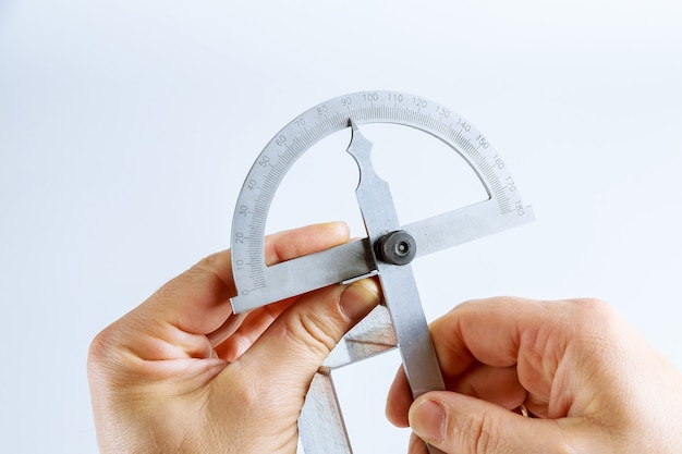 L'operatore misura l'angolo sul prodotto in metallo con un goniometro digitale. strumento e attrezzatura di piegatura della lamiera sottile su una priorità bassa bianca. goniometro digitale. Foto Premium
