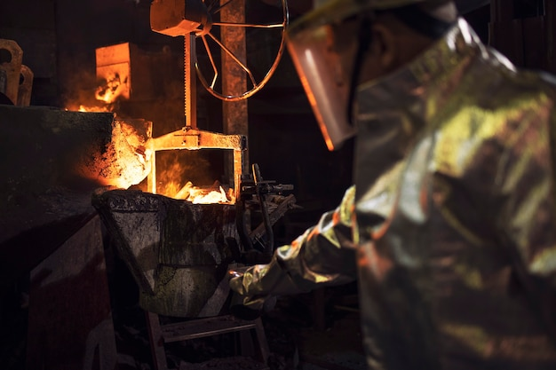 Lavoratore in abbigliamento protettivo che controlla il ferro fuso in fonderia. Foto Premium
