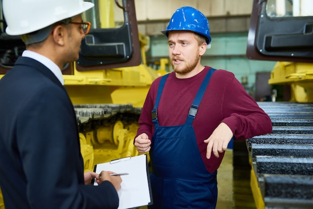 Lavoratore che parla con il responsabile nello stabilimento Foto Premium