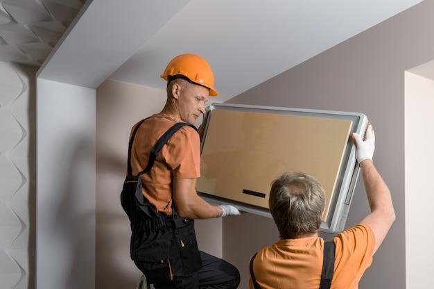 I lavoratori stanno installando un sistema split per un sistema di condizionamento domestico. Foto Premium