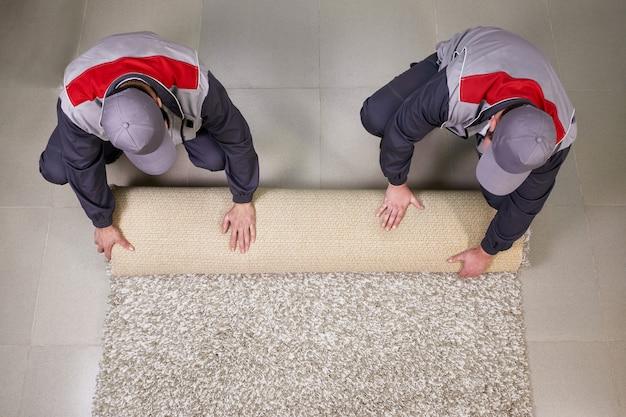 Lavoratori che rotolano tappeto sul pavimento a casa, vista da sopra Foto Premium