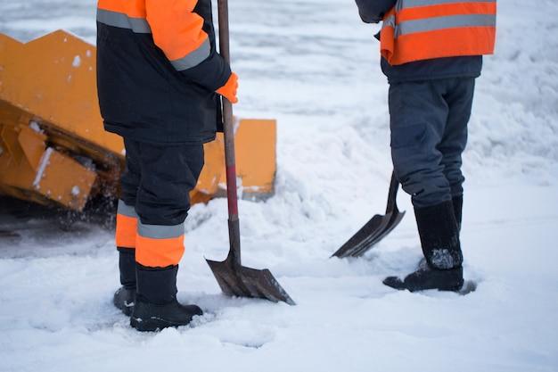 I lavoratori spazzano la neve dalla strada in inverno Foto Premium