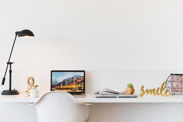 Luogo di lavoro con il computer portatile sul tavolo a casa Foto Premium