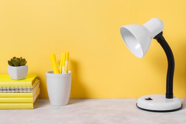 Disposizione dell'area di lavoro con libri e lampada Foto Premium