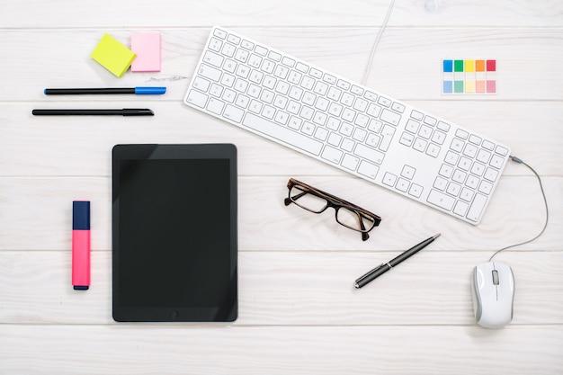 Area di lavoro con tastiera, tablet e articoli per ufficio su bianco Foto Premium