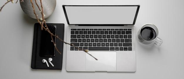 Area di lavoro con laptop mock-up, auricolare wireless, agenda, tazza di caffè e vaso Foto Premium