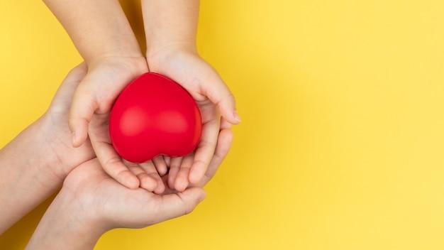 Mani della giornata mondiale della salute, dell'adulto e del bambino che tengono concetto rosso del cuore, di sanità, di amore e di assicurazione sulla famiglia Foto Premium