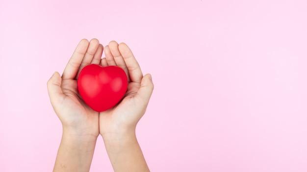 Giornata mondiale della salute, mani del bambino che tengono il cuore rosso, assistenza sanitaria, amore e concetto di assicurazione familiare Foto Premium