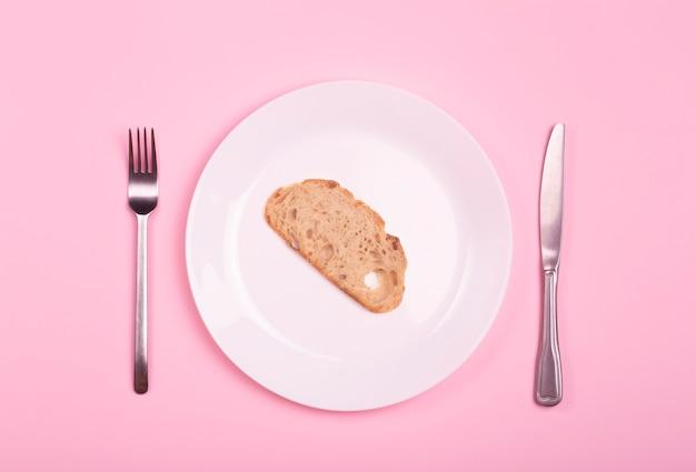 Concetto di fame e povertà nel mondo. un pezzo di pane su un piatto vuoto su un tavolo rosa. Foto Premium