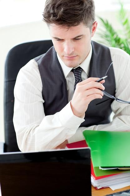 Preoccupato medico maschio guardando il suo computer portatile Foto Premium
