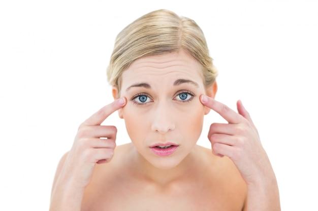 Giovane donna bionda preoccupata che la indica occhi con le sue dita Foto Premium