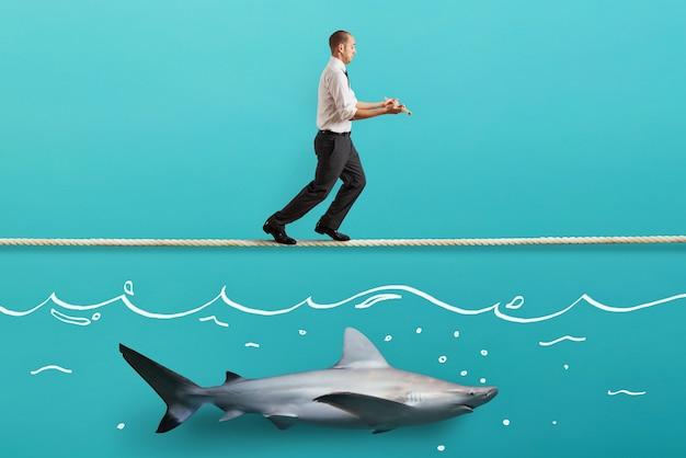 Preoccuparsi dell'uomo in equilibrio che cammina su una corda su uno squalo Foto Premium