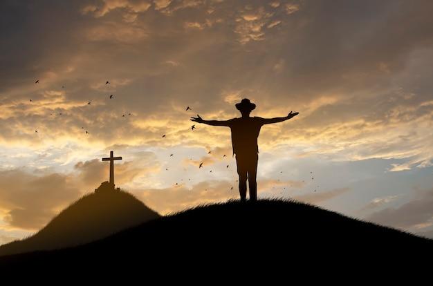 Concetto di culto: silhouette presso la croce di gesù. Foto Premium