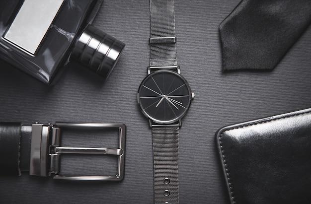 Orologio da polso, profumo, cintura, cravatta, portafoglio sulla tavola nera Foto Premium