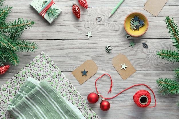 Sfondo di natale con ramoscelli di abete albero di natale, scatole regalo e decorazioni in rosso, bianco e verde. realizzare decorazioni fai da te a rifiuti zero a casa. Foto Premium
