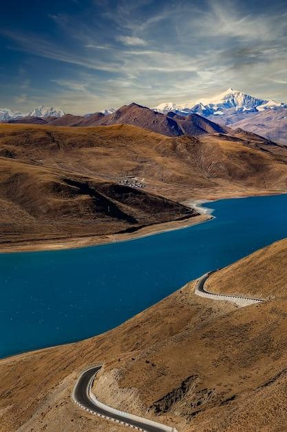 Yamdrok yumtso lago e strada in tibet con sottili nuvole bianche nel cielo Foto Premium