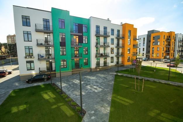 Cortile tra condomini residenziali con prati di erba verde e moderne abitazioni piatte. sviluppo immobiliare. Foto Premium